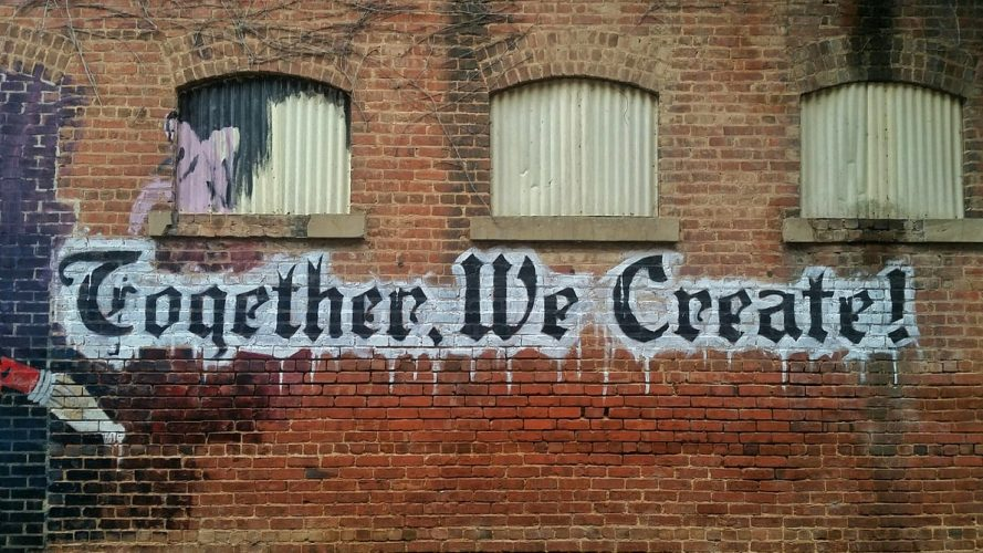 """""""Together, we create!"""" on brick wall - Photo by"""